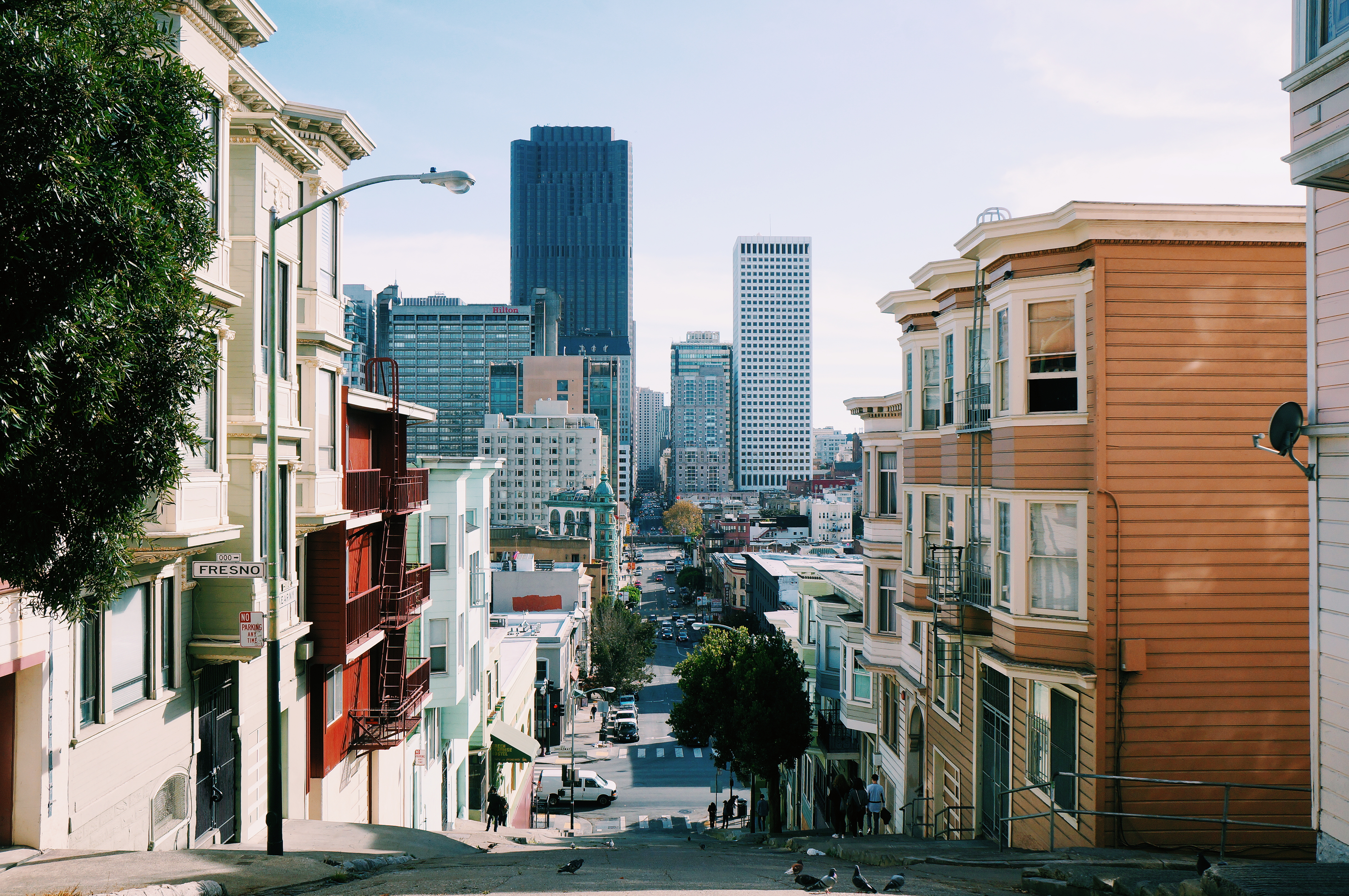 A view down a street in San Francisco. There are three to four story buildings on either side of the street and skyscrapers in the distance.