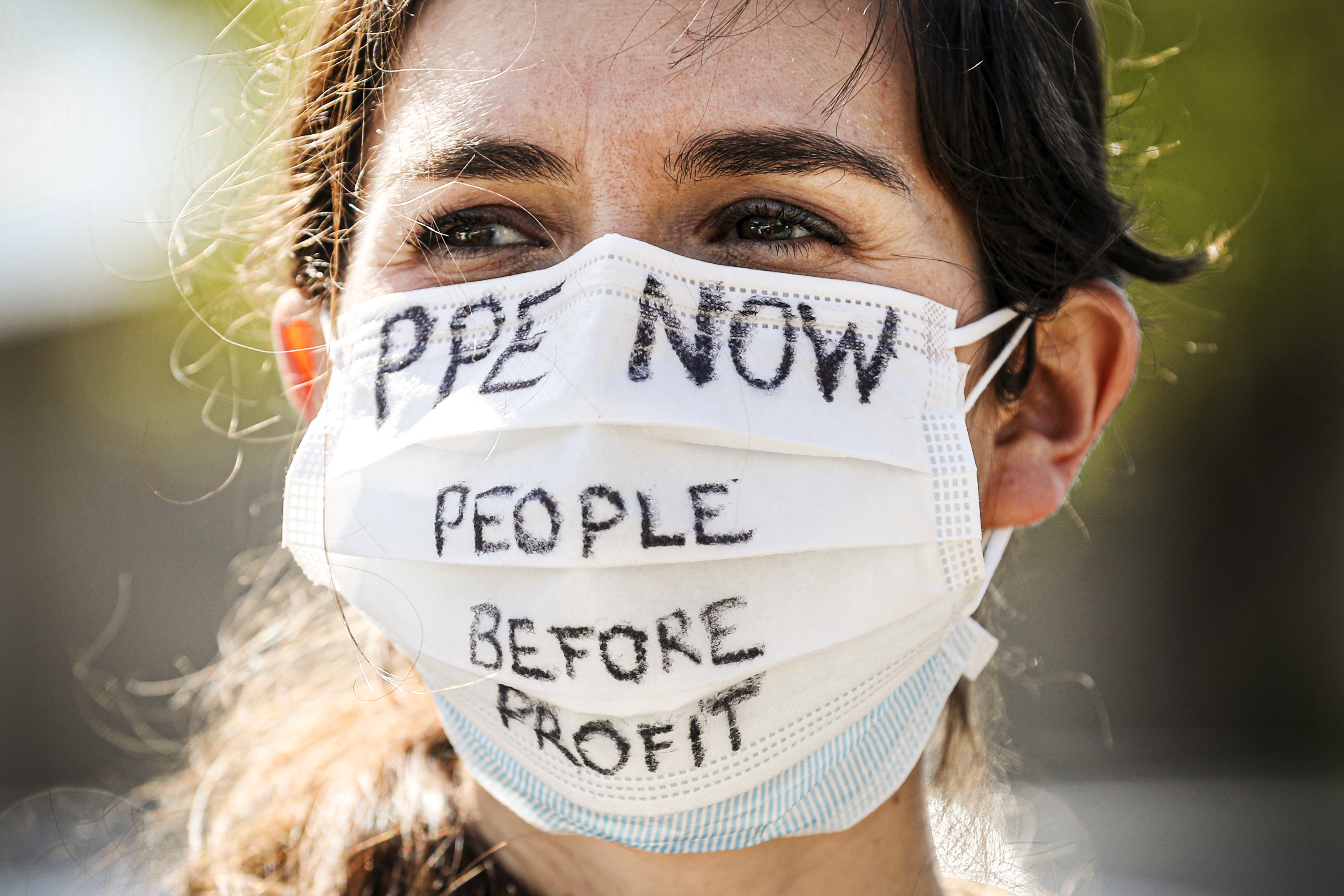 "A person in a breathing mask that reads ""PPE now, people before profit."""