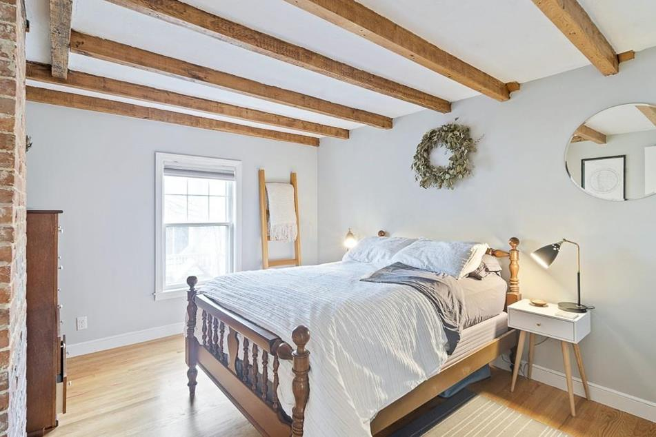 A bedroom with a bed and a beamed ceiling.