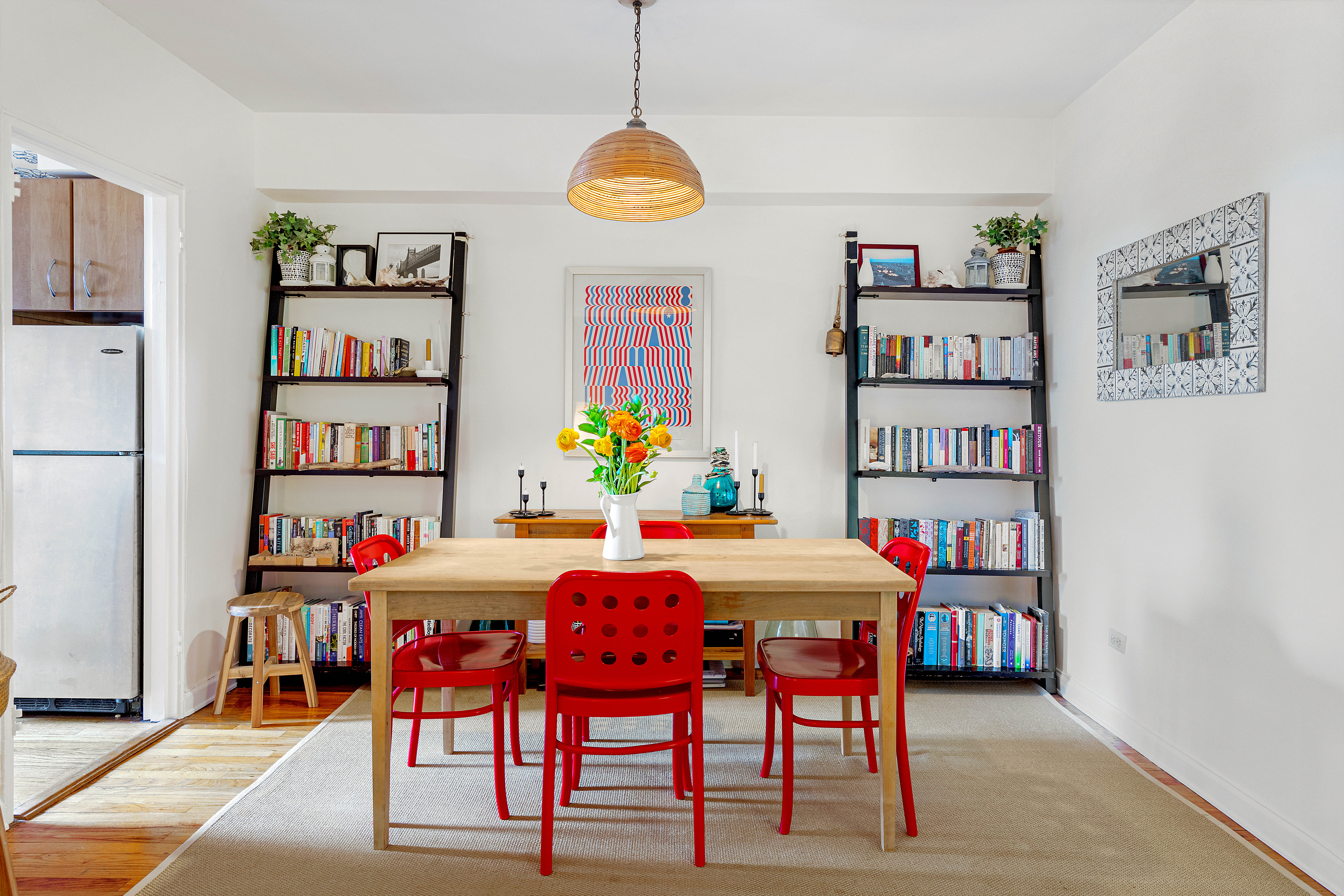 A dining area with a wooden table, four red chairs, two bookshelves, and a light brown rug.