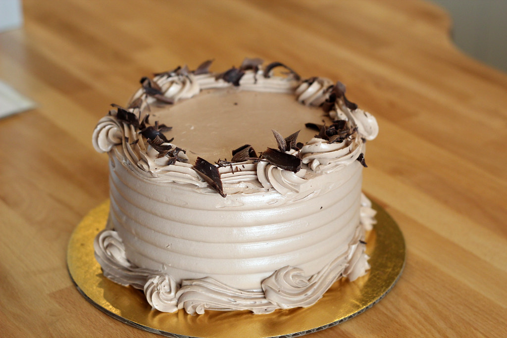 A cake with chocolate frosting and chocolate shavings sits on a wooden counter