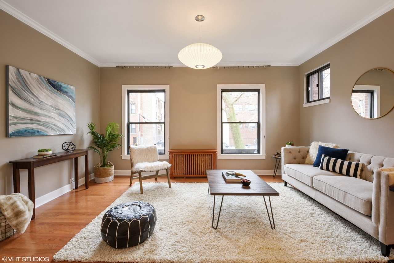 An image of a living room with a couch, coffee table, a console, paper light fixture, and two windows.