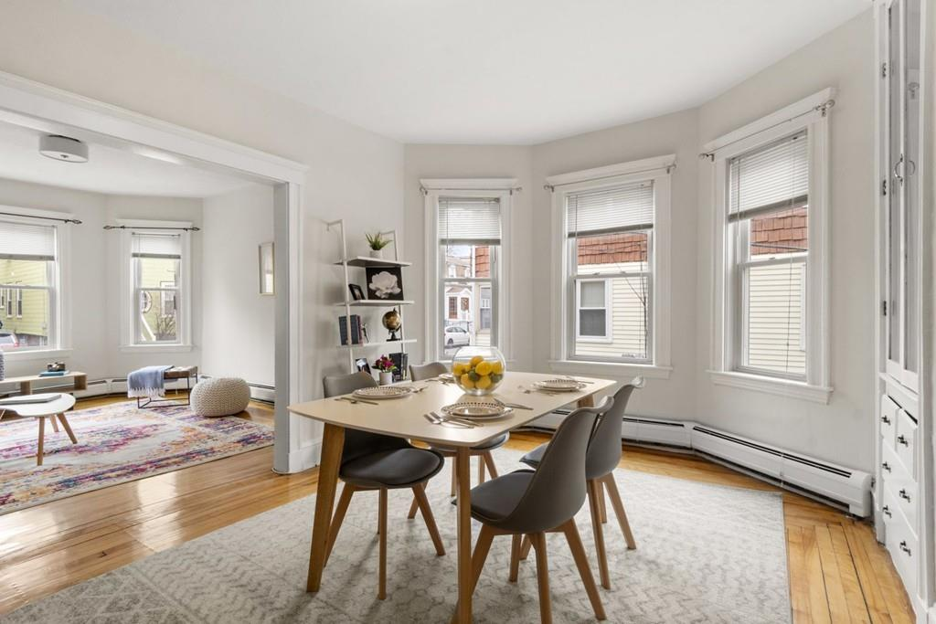 A sunny dining room with a bay window and a table and chairs.