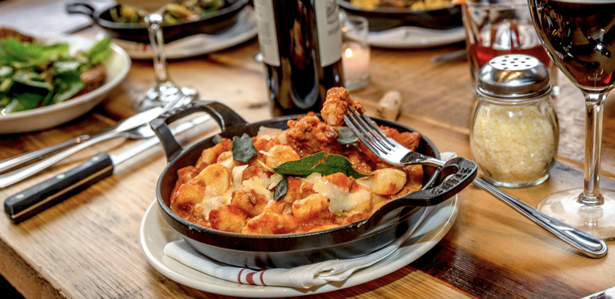 A cast-iron pan is filled with pasta, and sits atop a wooden table. It is accompanied by silverware, a shaker of parmesan, and a bottle of wine.