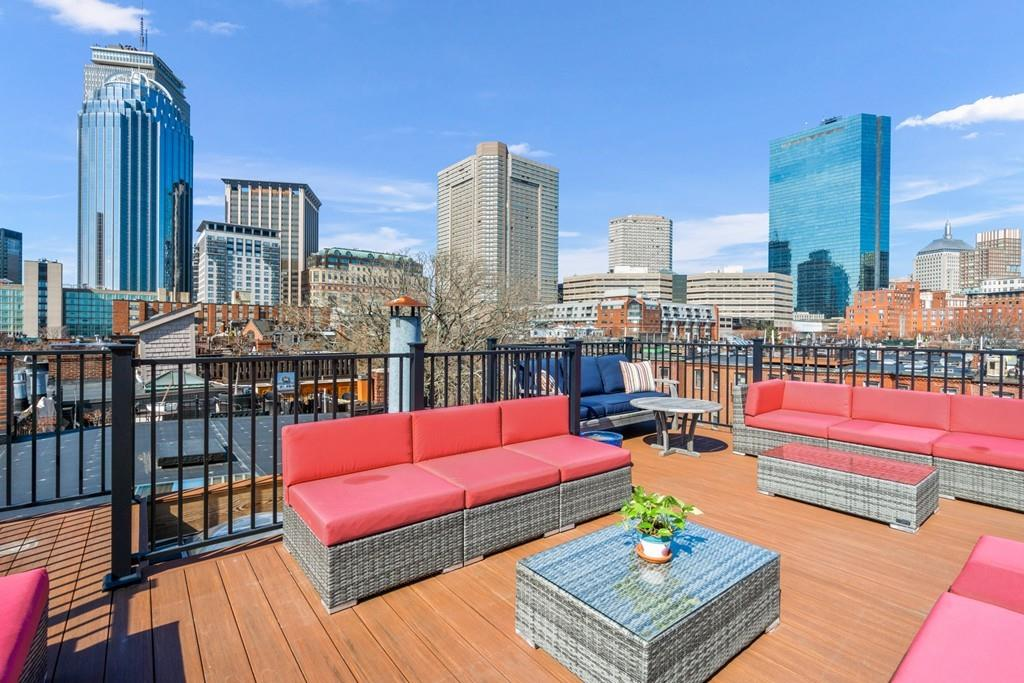 A roof deck with furniture and skyscrapers in the distance.