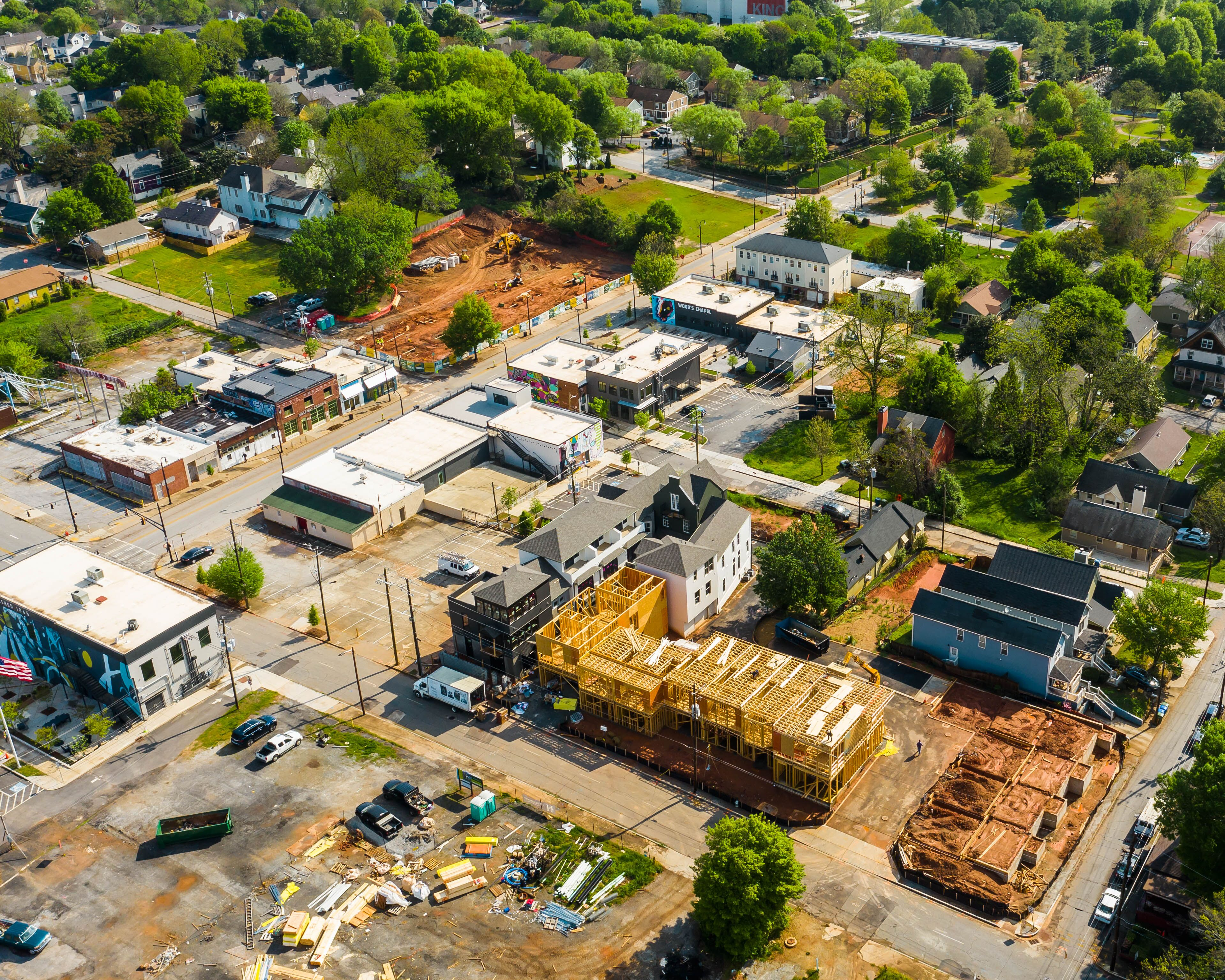 An aerial photo of new development with large construction sites and homes and buildings.