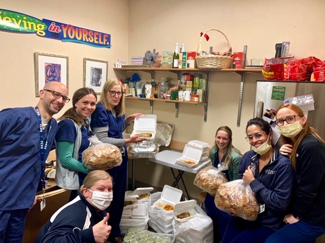 group of people in scrubs and medical masks holding takeout containers of food