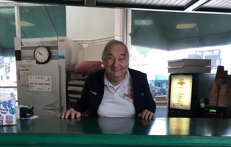 Doughnut shop owner Stan Berman stands behind his green counter.