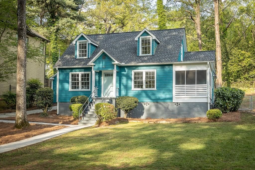 A little sky blue bungalow in the woods beneath huge trees in Atlanta, with green grass all around.