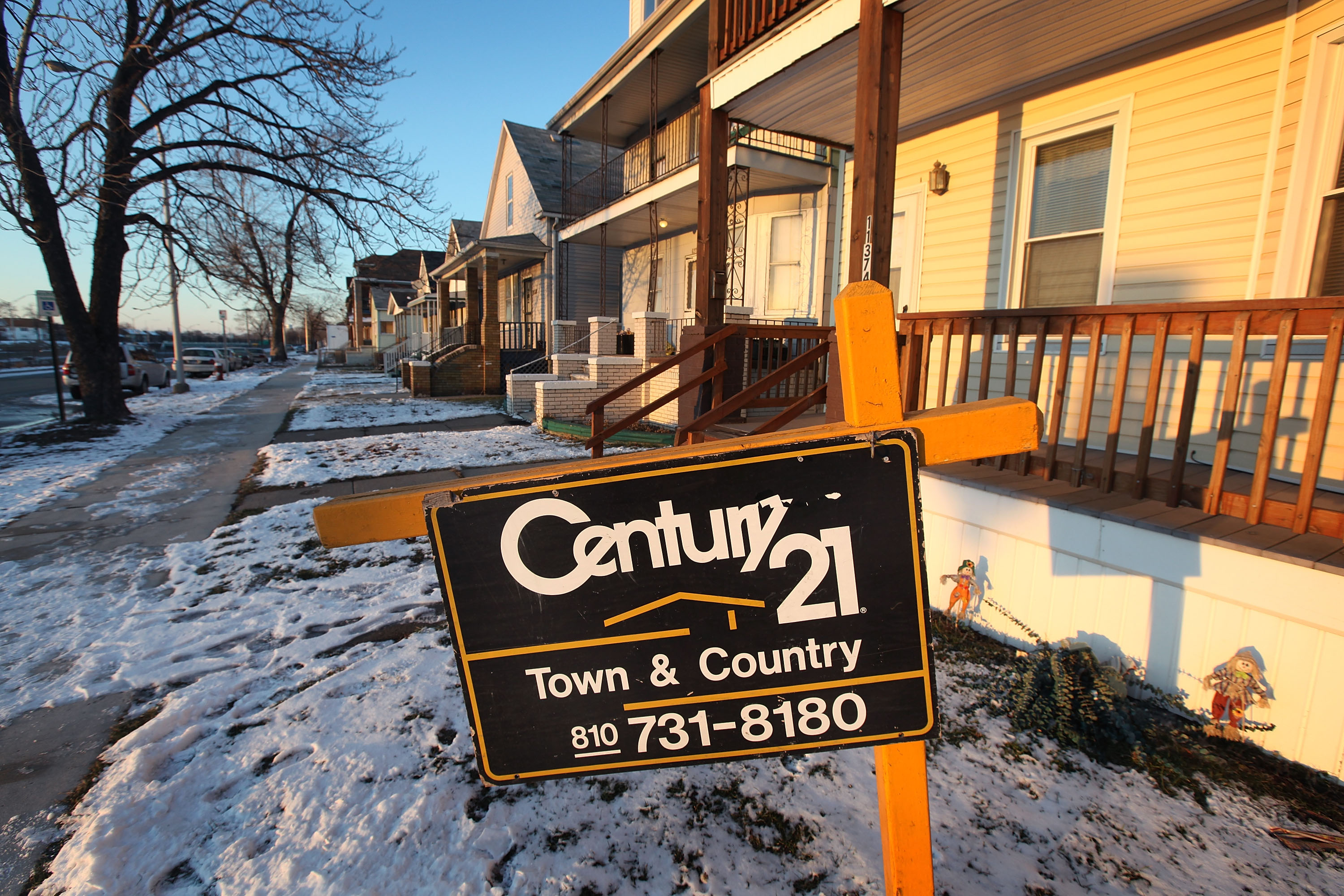 """A snow-covered residential street with a """"for sale"""" sign outside a home with white vinyl siding."""