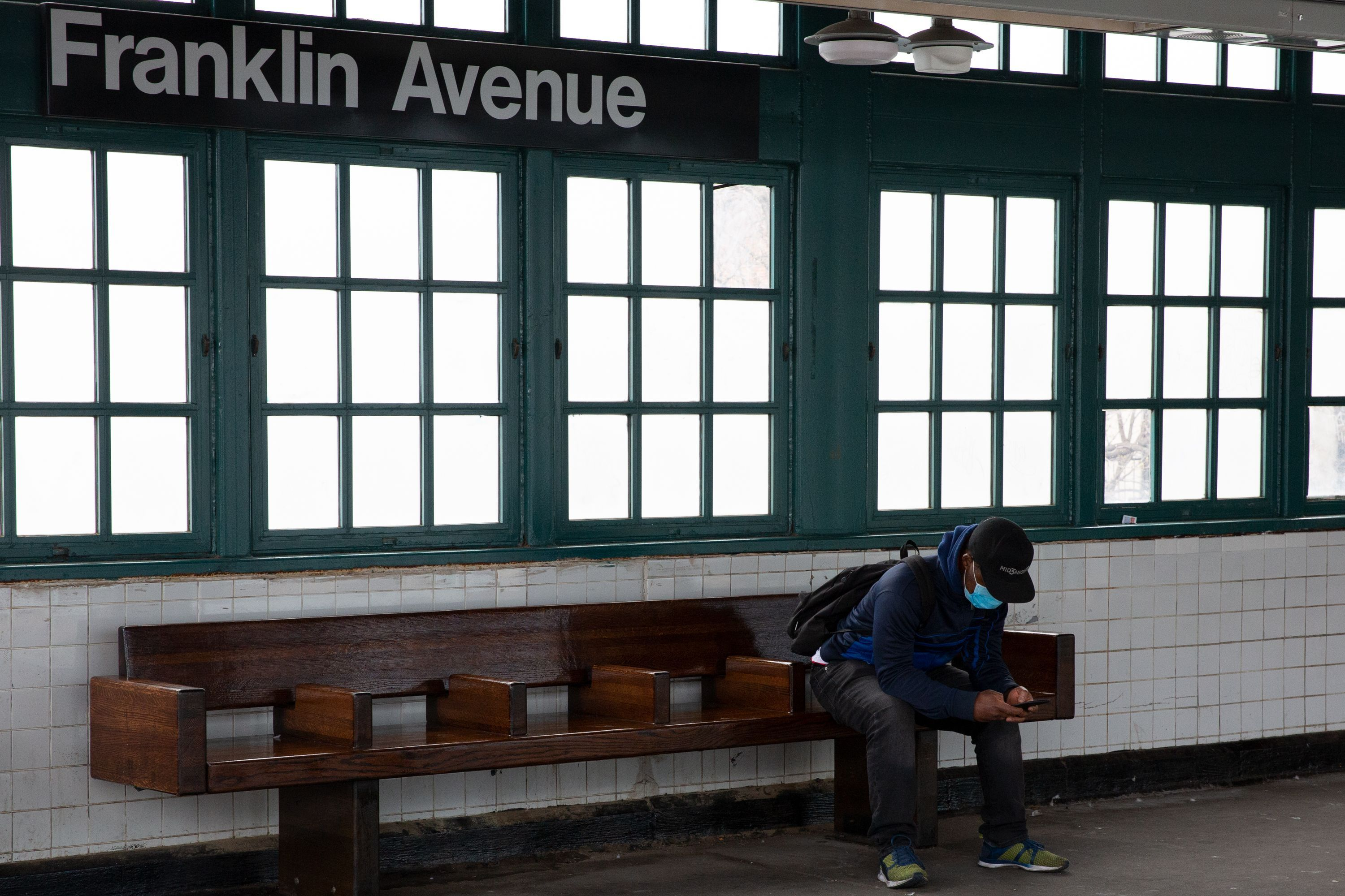 A man waits for the Franklin Avenue shuttle during the coronavirus outbreak.