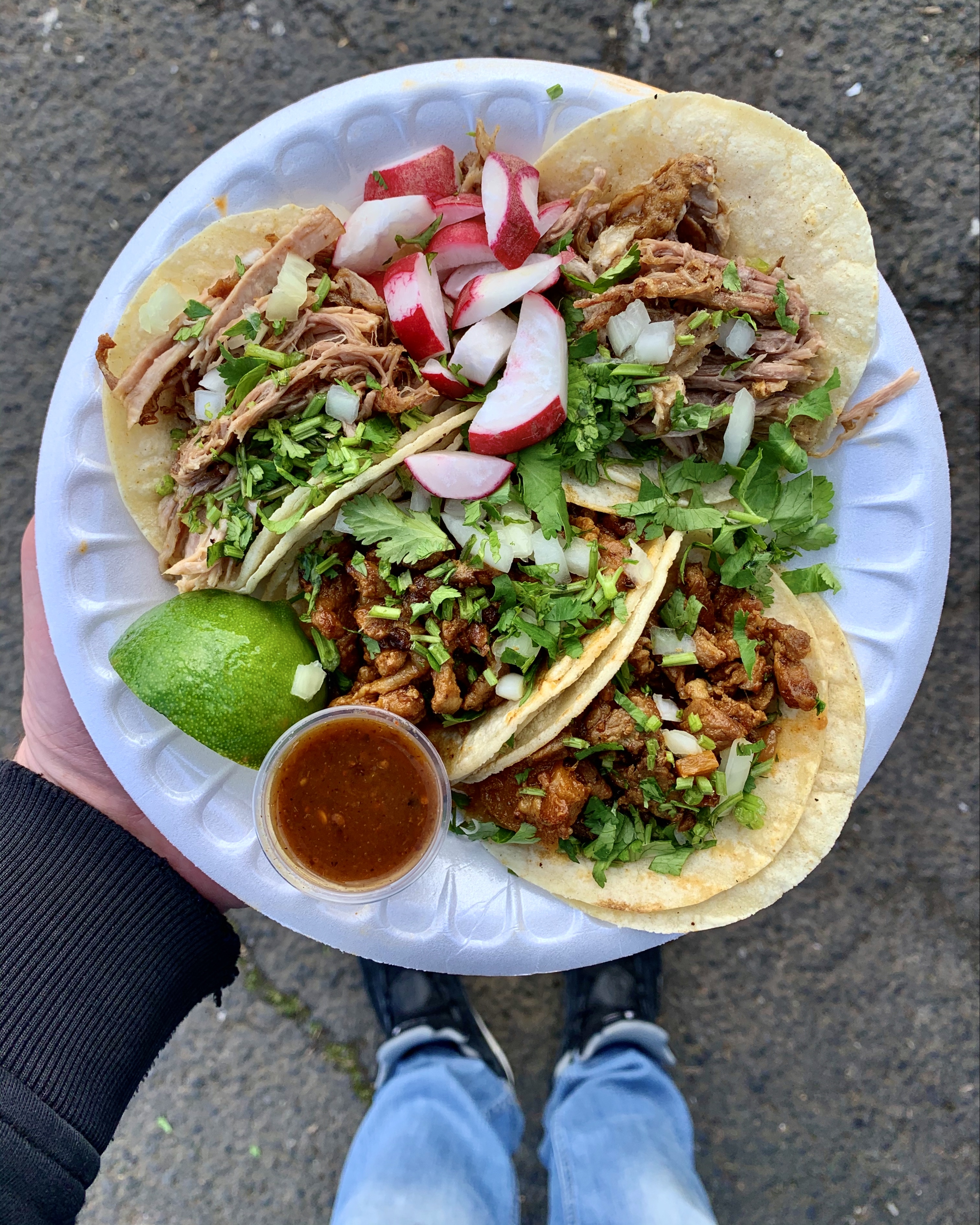 A man holds a plate with four tacos, a lime, and a thing of salsa on a white disposable plate. These tacos are from La Morenita Ricos Tacos.
