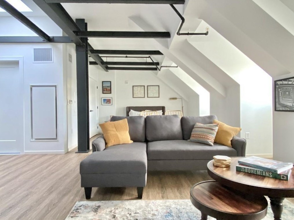 A long living room with an arched ceiling and exposed beams, and there's an L-shaped couch.