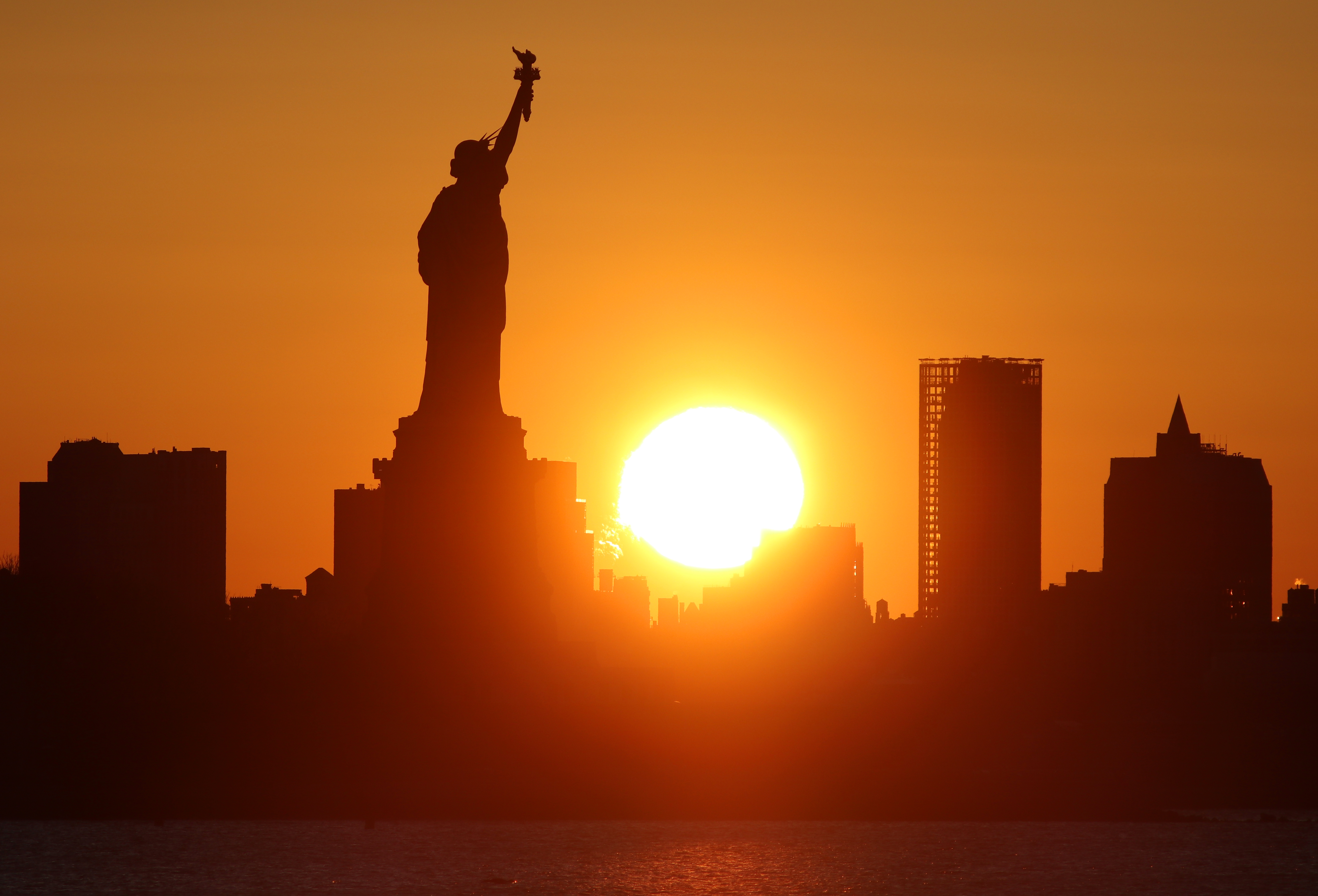 Sunrise Behind the Statue of Liberty in New York City