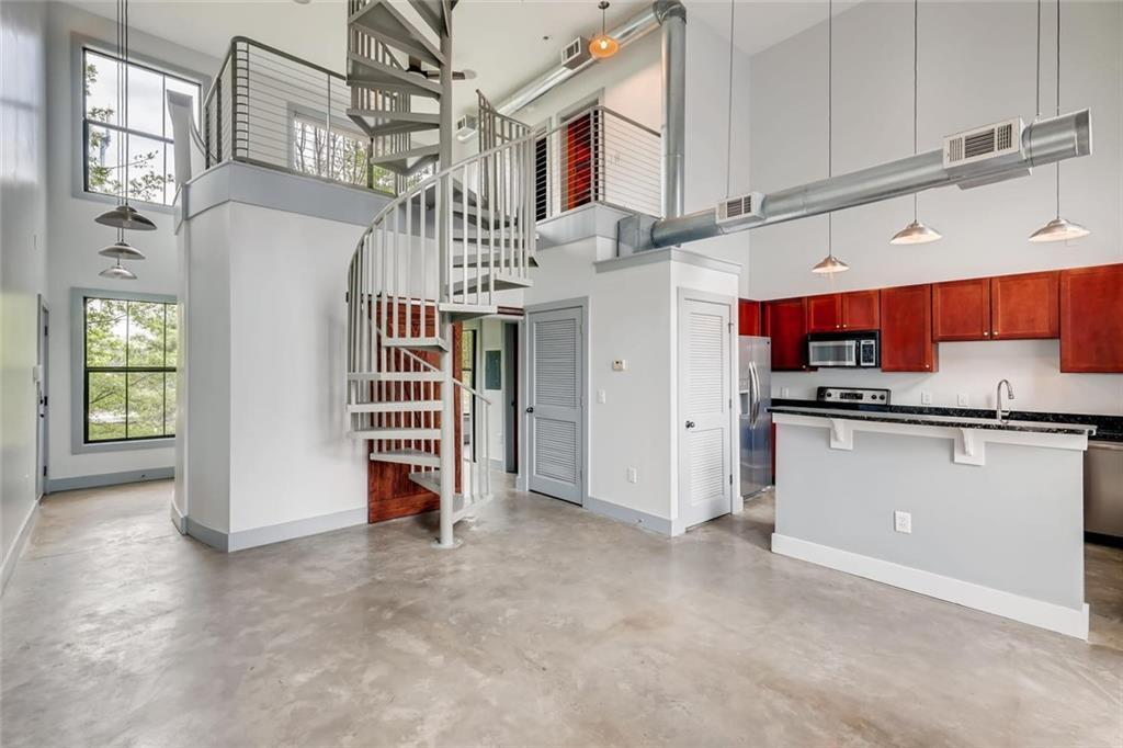 Large two-story room with kitchen to the right, spiral staircase in the middle and floor-to-ceiling windows in the background.