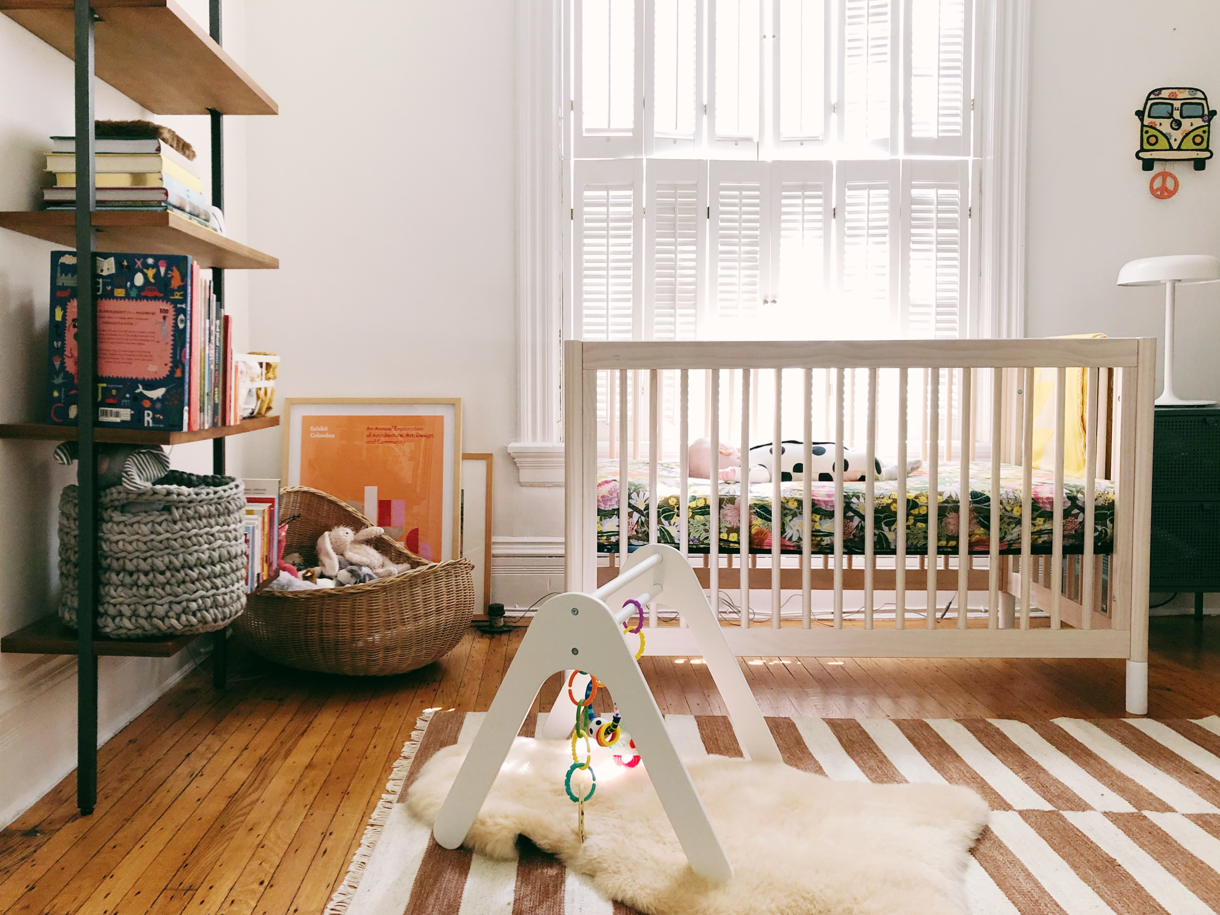 A white-walled room contains a white crib with a baby in it, a bookshelf holding books and a basket, a brown and white striped area carpet on a hardwood floor, and a white baby's jungle gym.