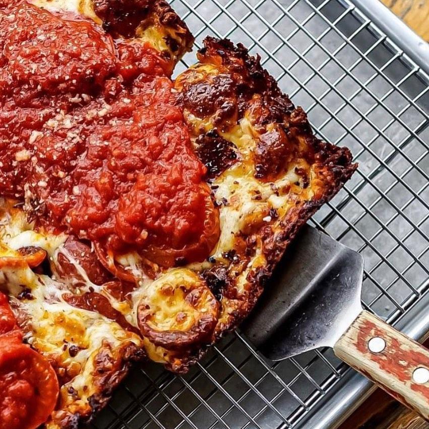 A spatula holding up a slice of Detroit-style pizza from Nina & Rafi in Atlanta
