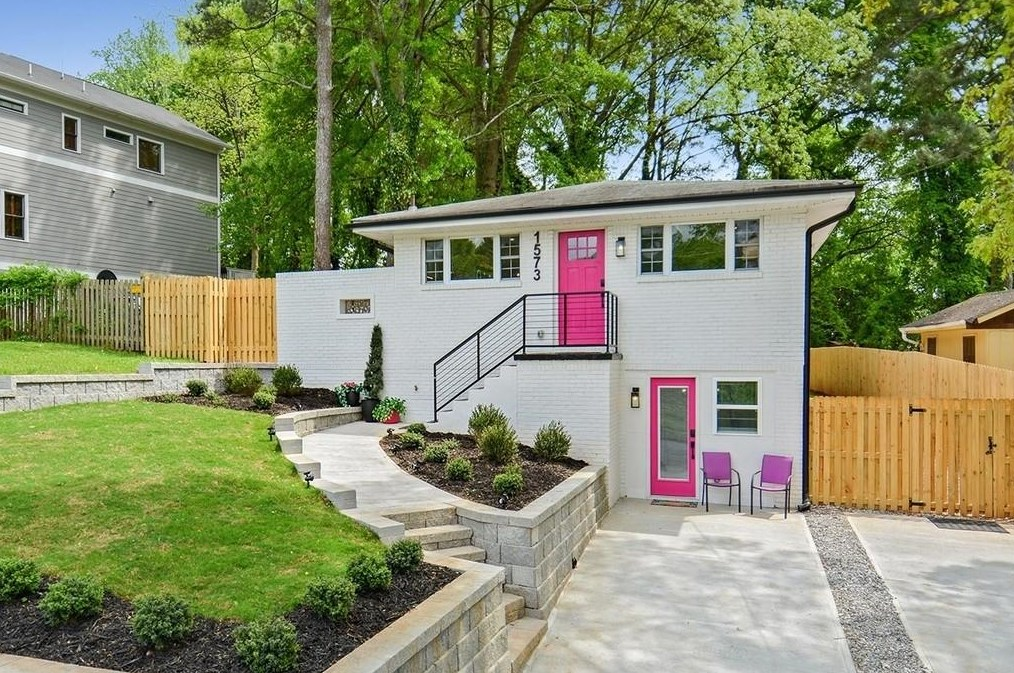 A white home with two pink doors and a sloping green grass hill, with stone steps.