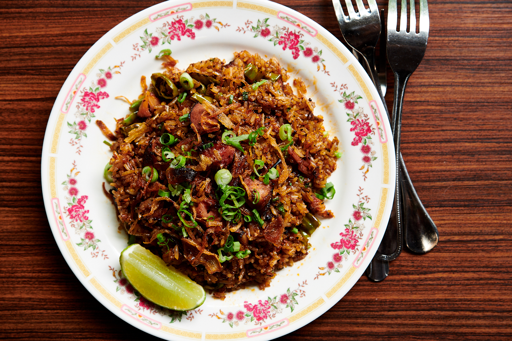 A picture of a plate of barbecue fried rice with a side of lime. The rice comes with a handful of sliced scallions.