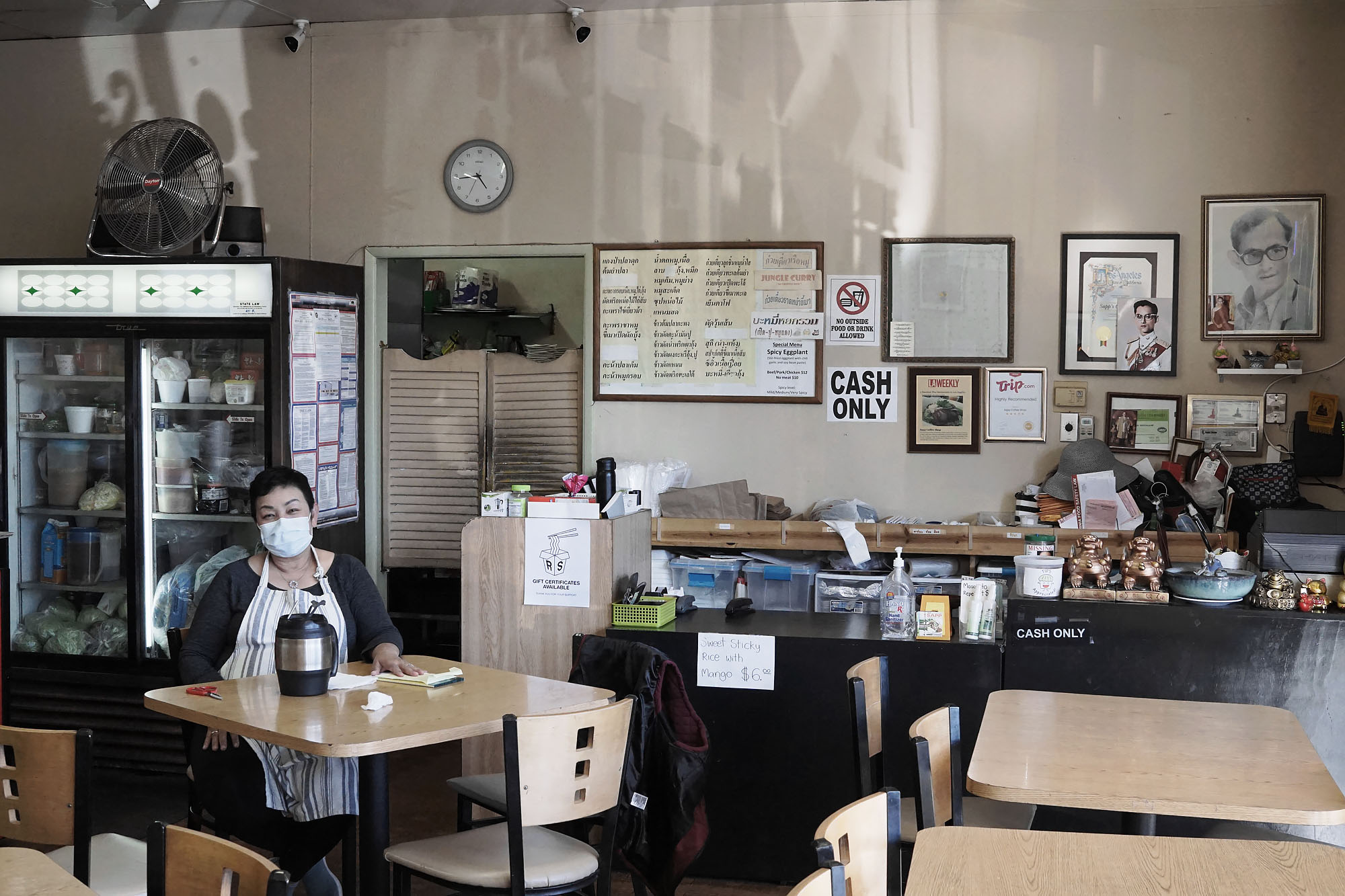 A lone owner sits inside of a restaurant wearing a mask during coronavirus.