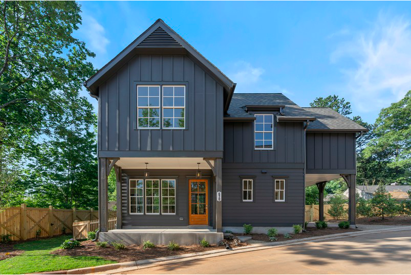 A dark gray new home with blue skies overhead.