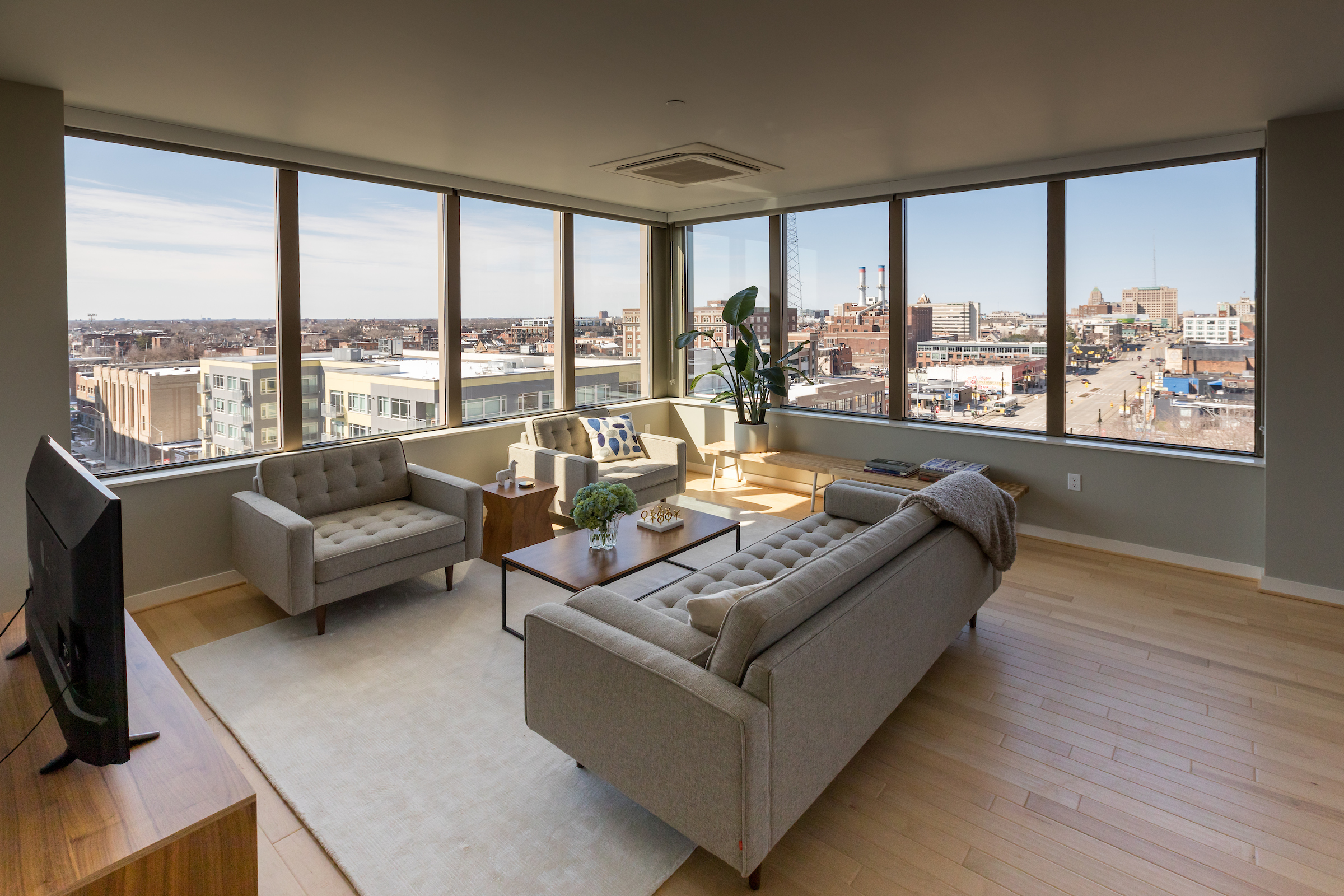 Inside a hi-rise apartment with views of the city out the large windows. A white couch faces two white chairs with a glass coffee table in between.