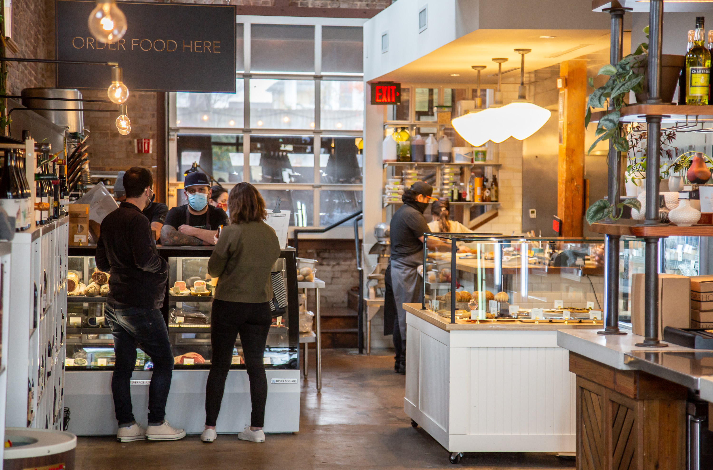The newly opened Staplehouse market on Edgewood Avenue in Atlanta with two people ordering meats and cheese at the counter from a masked employee during the pandemic of 2020