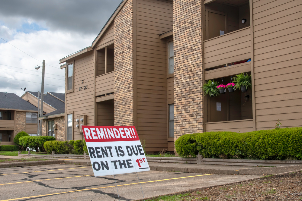 """A sign in the parking lot of an apartment complex reminds renters that """"Rent is due on the 1st."""""""