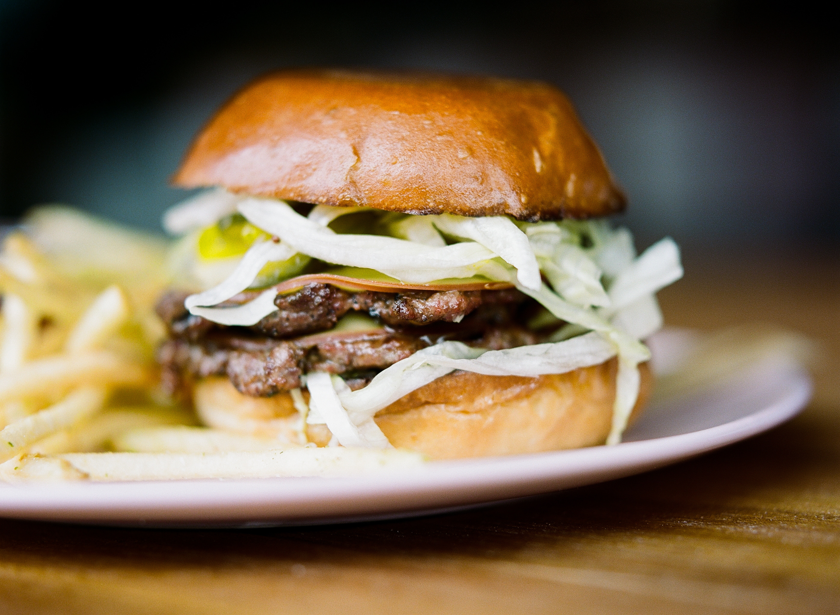 """A closeup sideview of Eden Hill Provisions's """"Big Max"""" burger with a side of fries out of focus."""