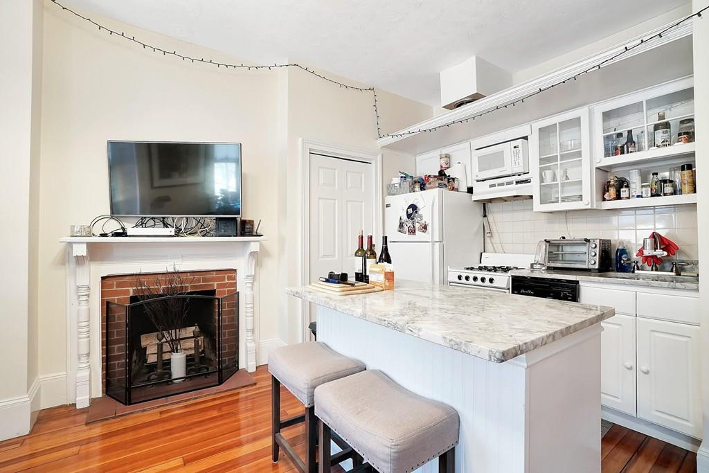 A small, open living room-kitchen area with an island and a fireplace, and lots of cabinetry in the kitchen.