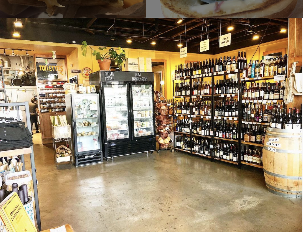 Shelves of wine and other bottles line the shelves at L'Oursin in Seattle, with a refrigerator in the center of the space