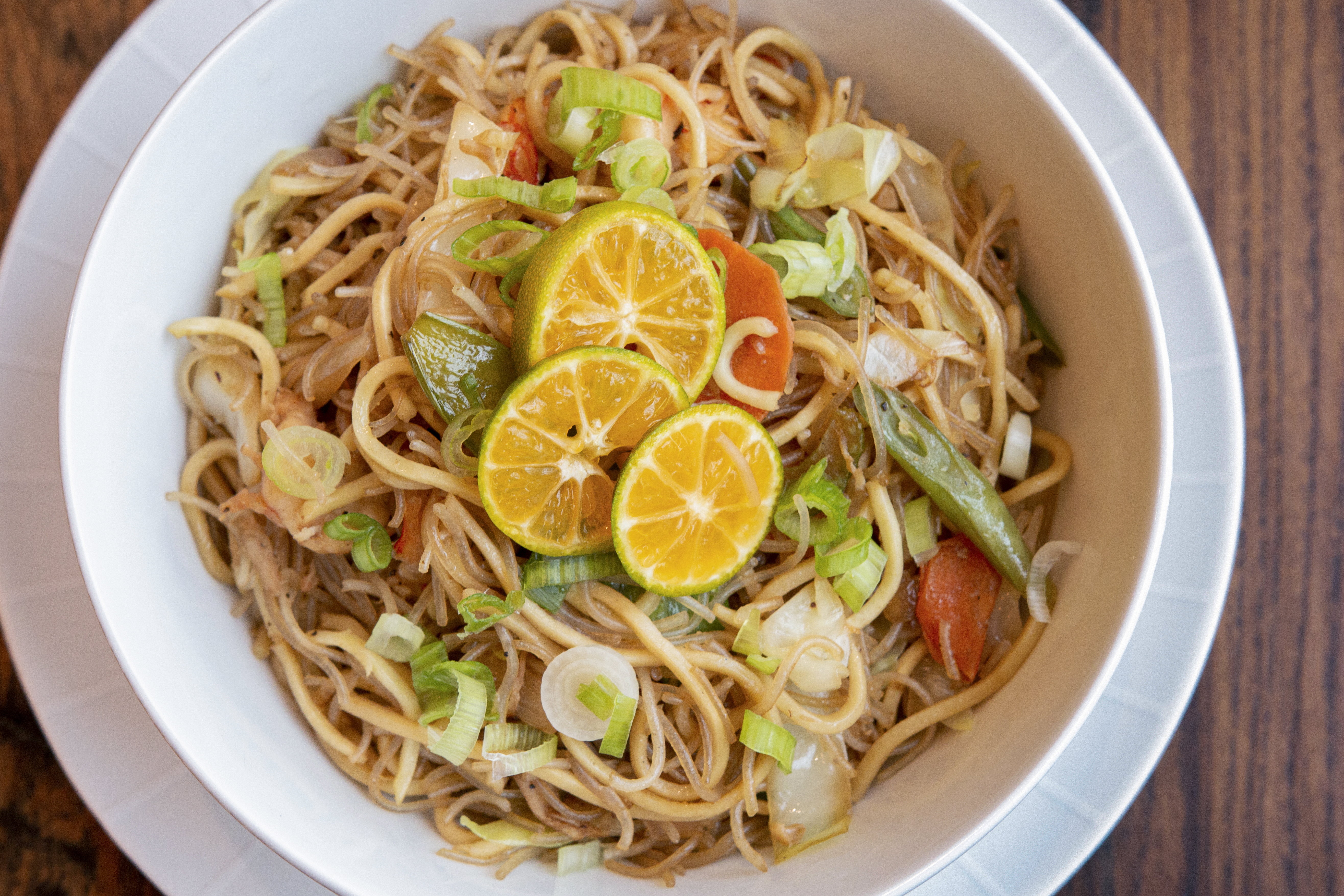 A bowl of pancit or Asian vermicelli sauteed in a wok with assorted vegetables, garnished with green onions and three slices of lemon