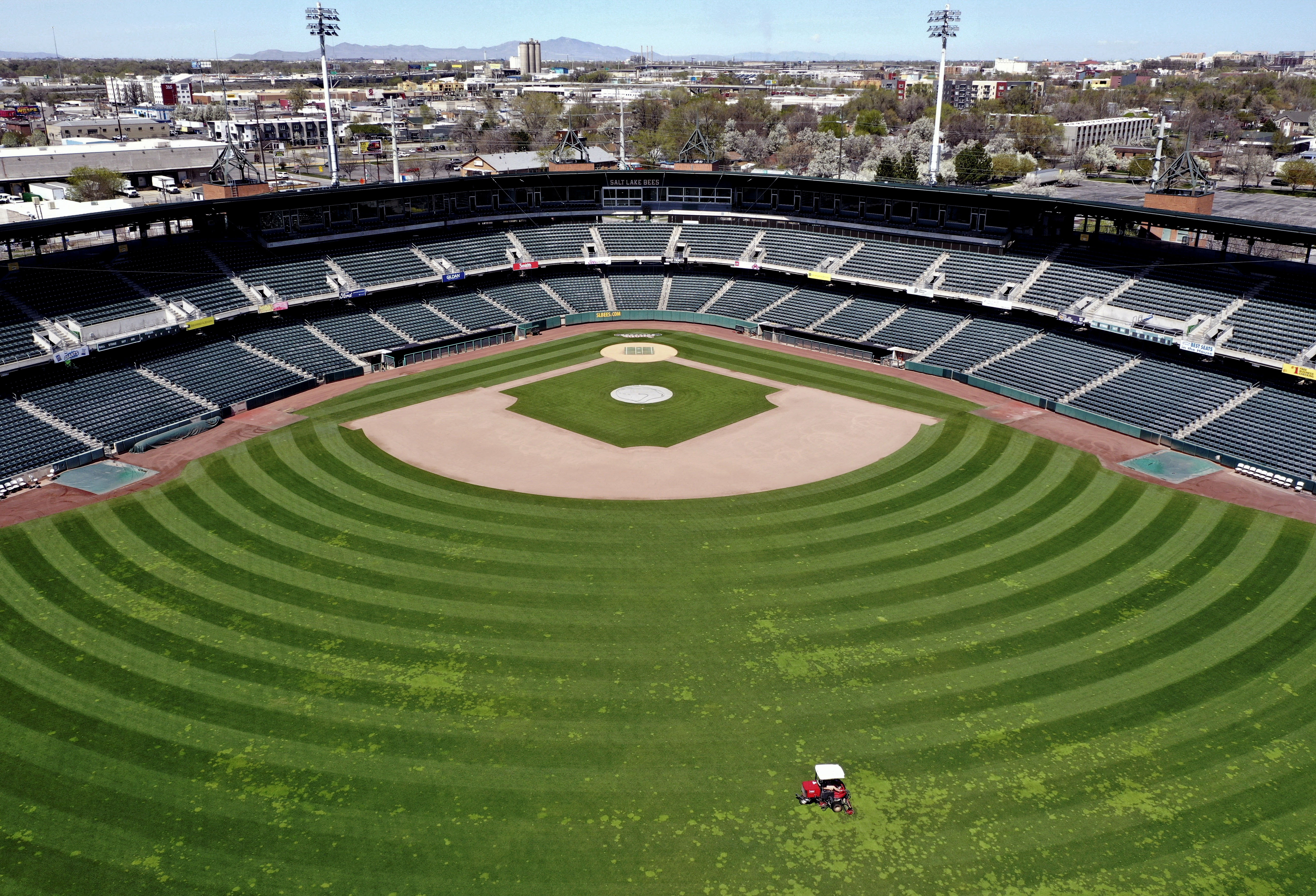 Brian Soukup, director of field operations, mows the field at Smith's Ballpark in Salt Lake City on Wednesday, April 8, 2020. Soukup is intentionally keeping the discolored grass in an effort to save money until the season is a go.