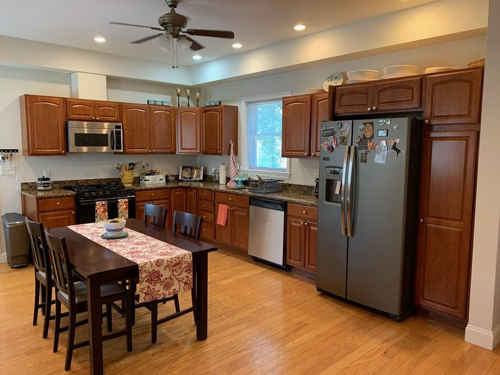 A sizable kitchen with a table and chairs.
