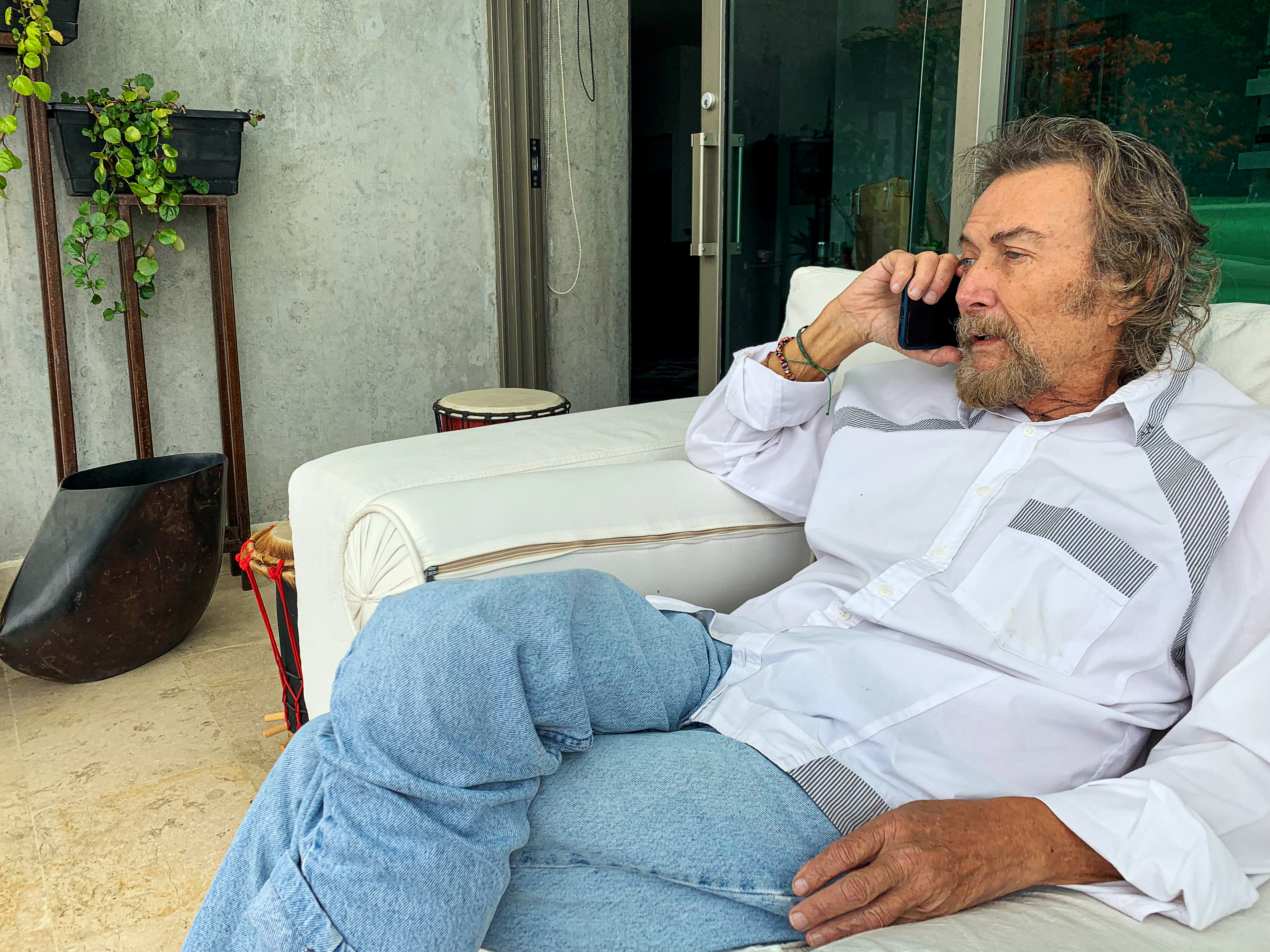 Diego Angel sits outside while talking on the phone