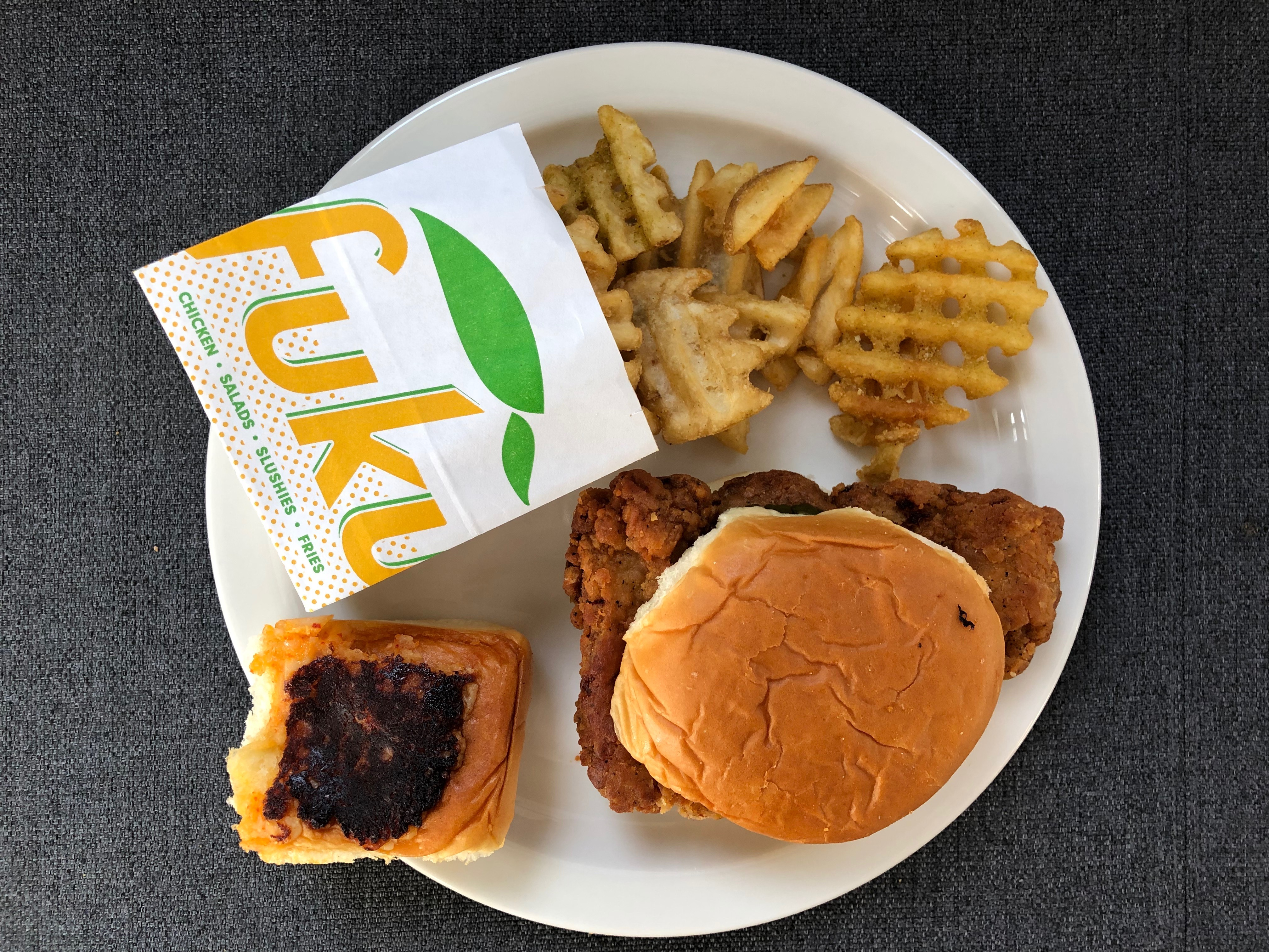 A paper plate with a fried chicken sandwich, cheese bread, and waffle fries inside a Fuku-branded carton.