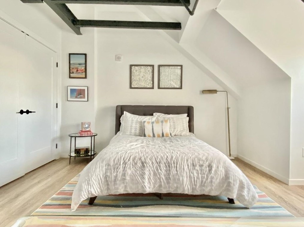 The bedroom area of a studio, with an arched ceiling with exposed beams and a bed.