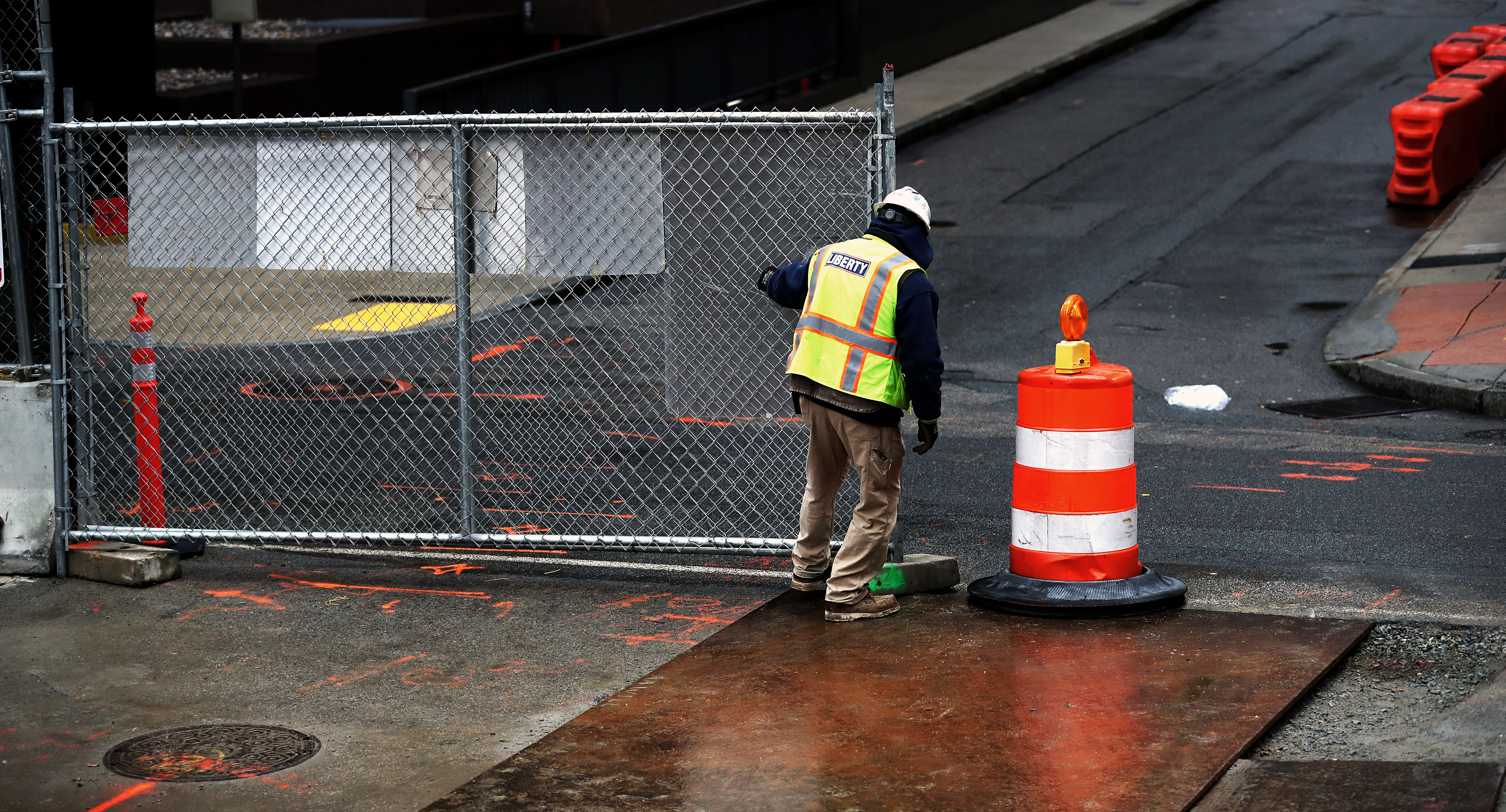 A lone construction worker closing a chain-link fence at a construction site, and there's an orange barrel next to him.