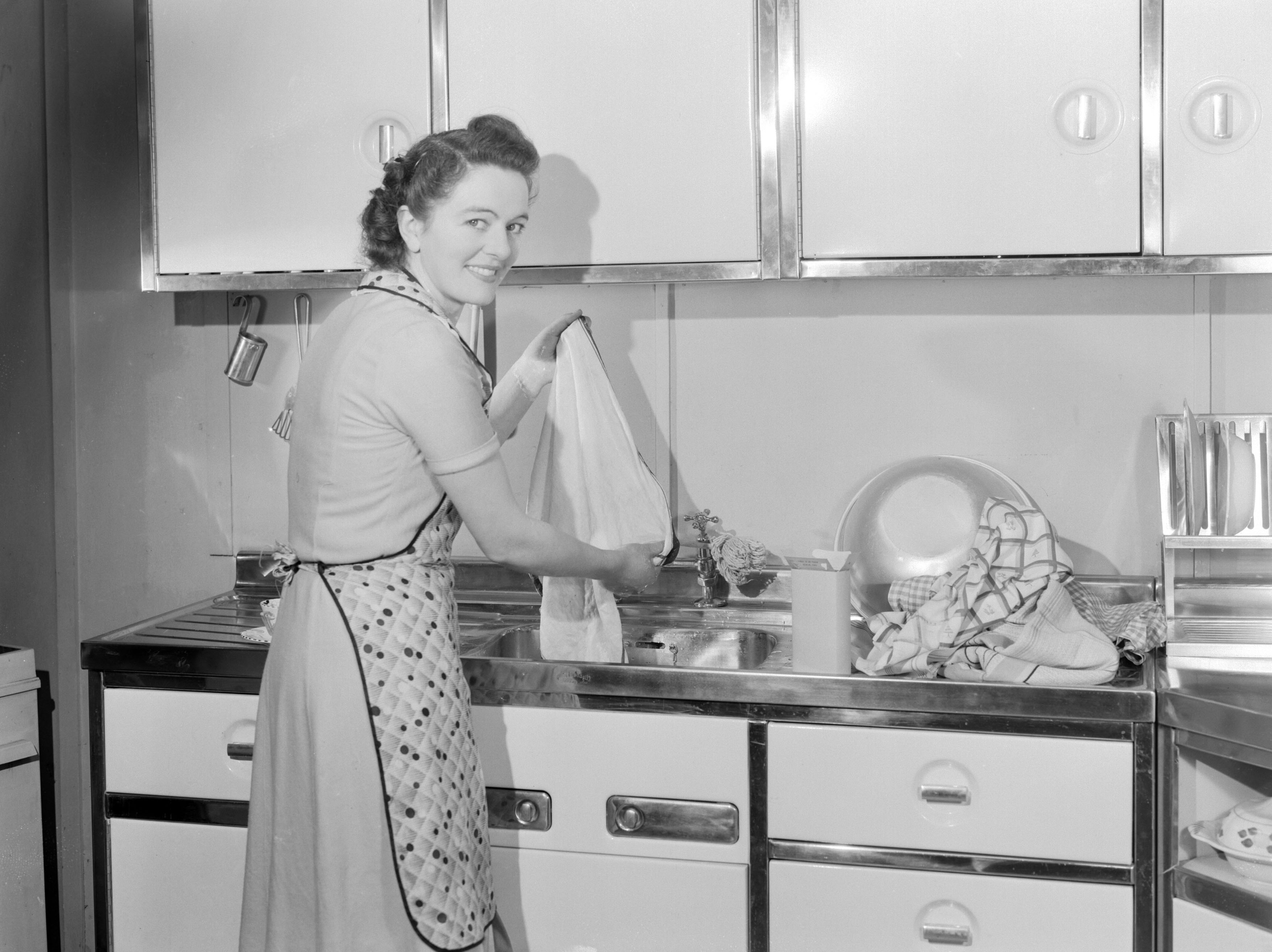 Woman washing cloths in a kitchen sink, 1950.