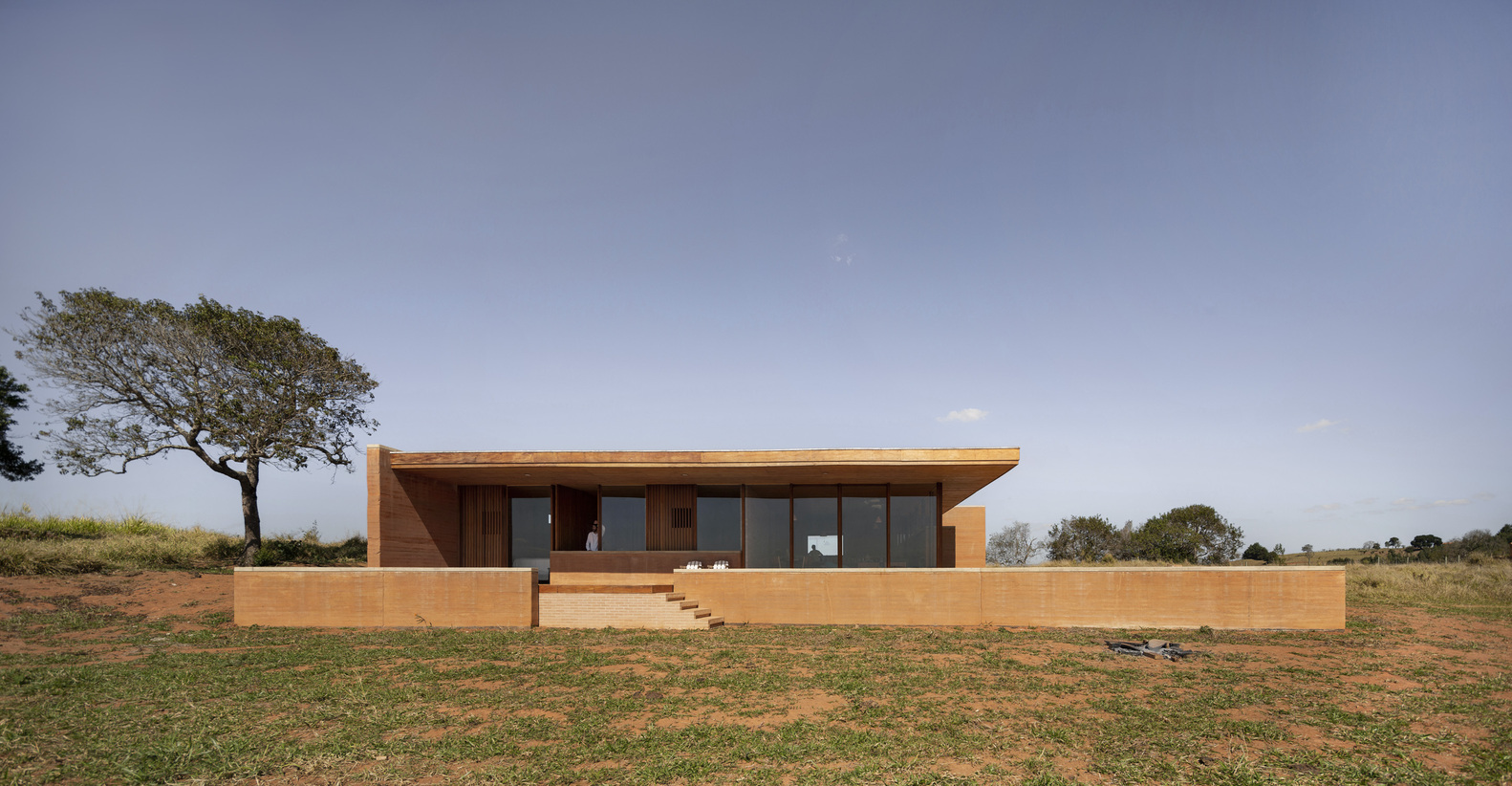 Flat-roofed rammed earth house sitting on hill.