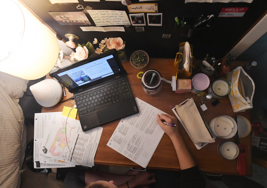 Aerial view of a desk with an open computer and a person holding a pen and writing