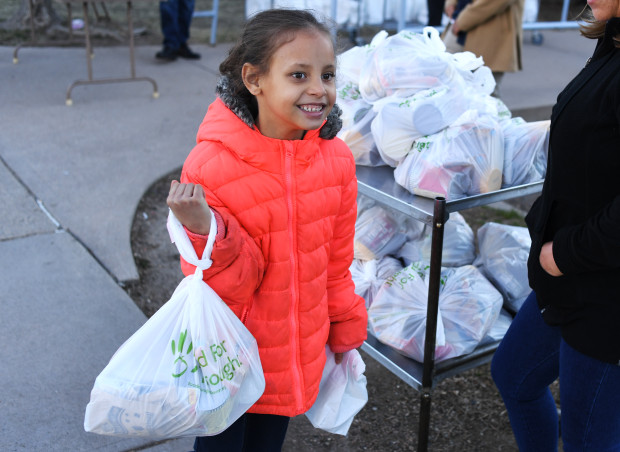 Da'vida Jones, 7, picks up a free meal and some extra food given out at Cowell Elementary on March 16, 2020 in Denver, Colorado.