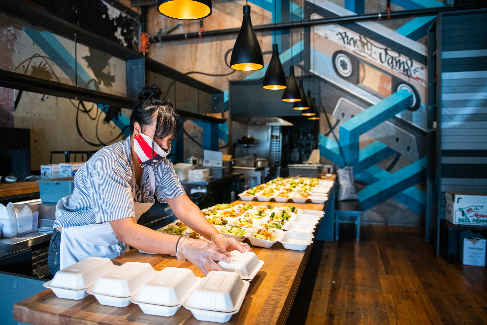 Diane Lam, wearing an American flag makeshift face mask and clear plastic gloves, prepares boxes of takeout to deliver to a homeless shelter. Standing in the empty dining room of Revelry, Lam pushes together the tables to accommodate the several boxes of food.