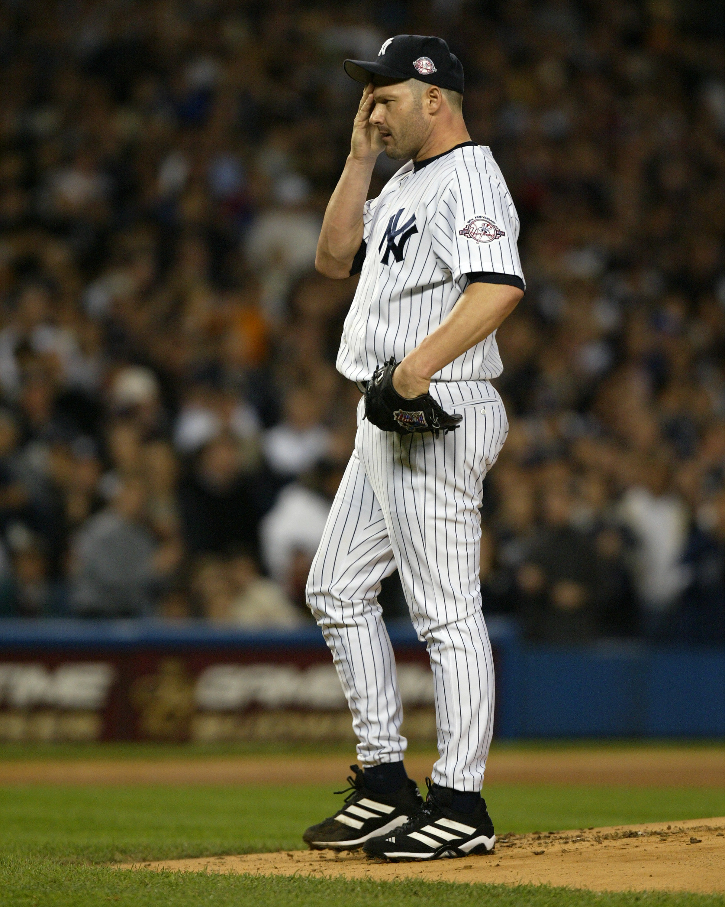 New York Yankees' starter Roger Clemens wipes his forehead a