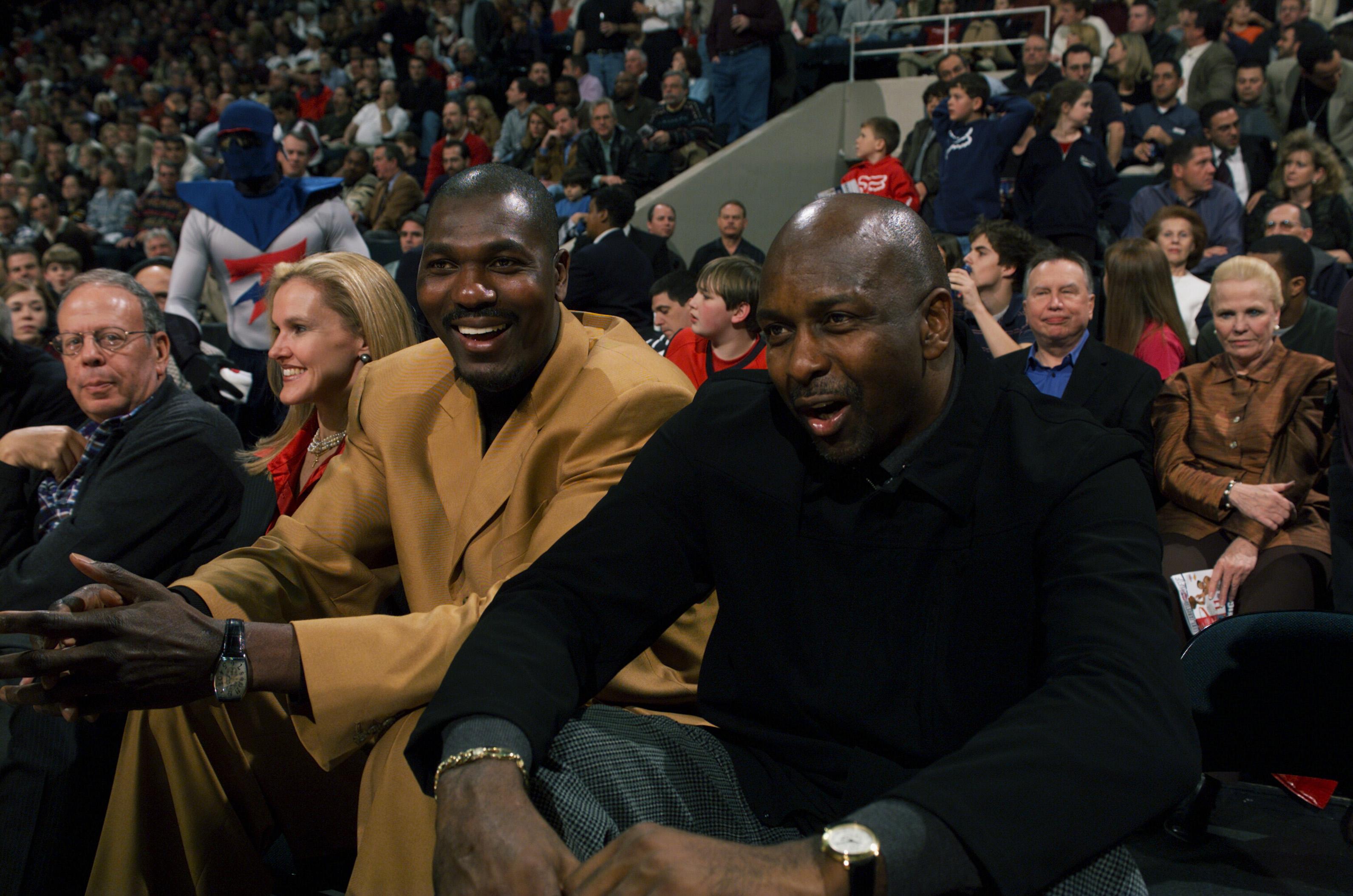 Hakeem Olajuwon and Moses Malone sit courtside