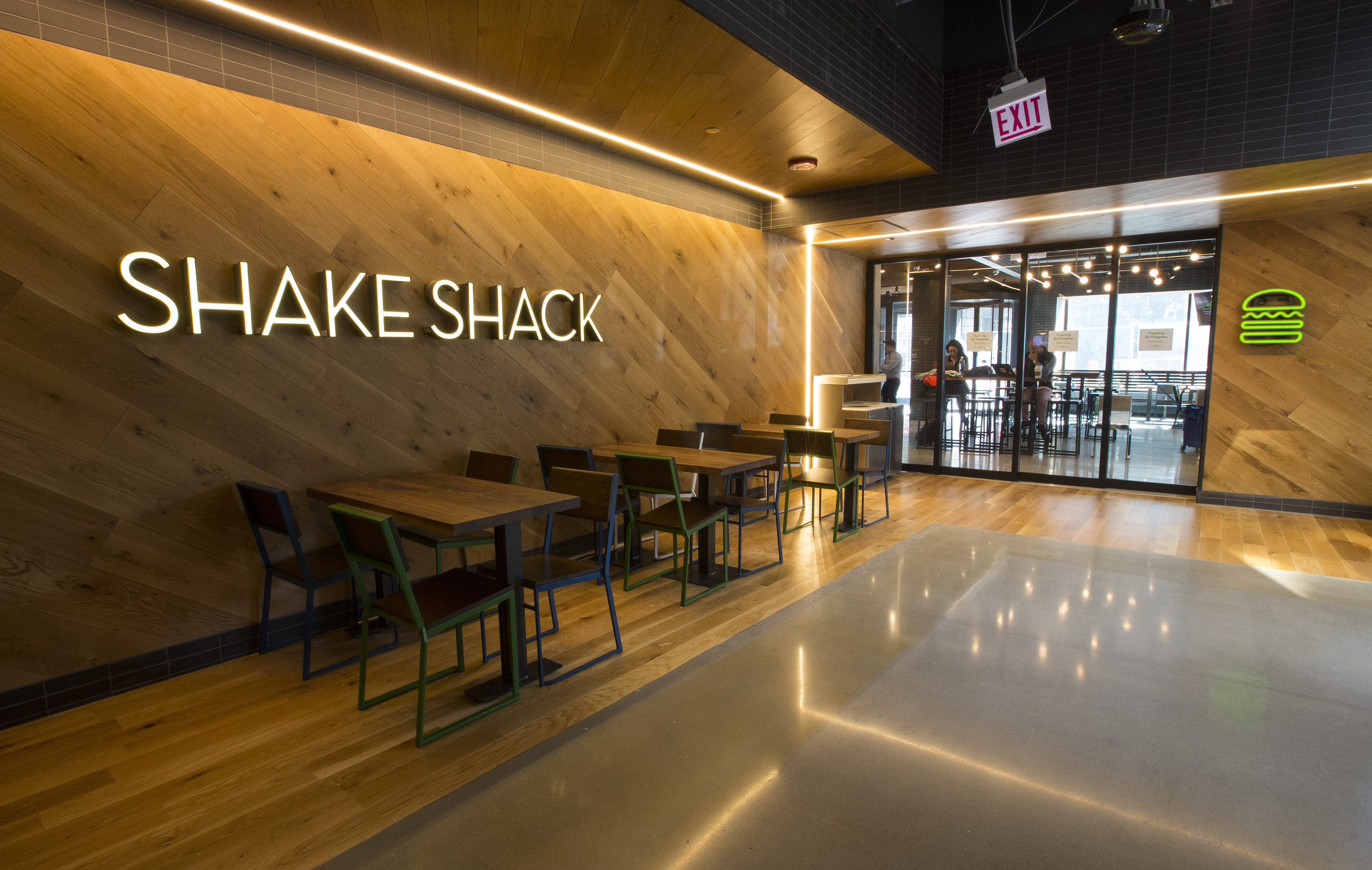The hallway entrance to a Shake Shack with light wood and neon signs.