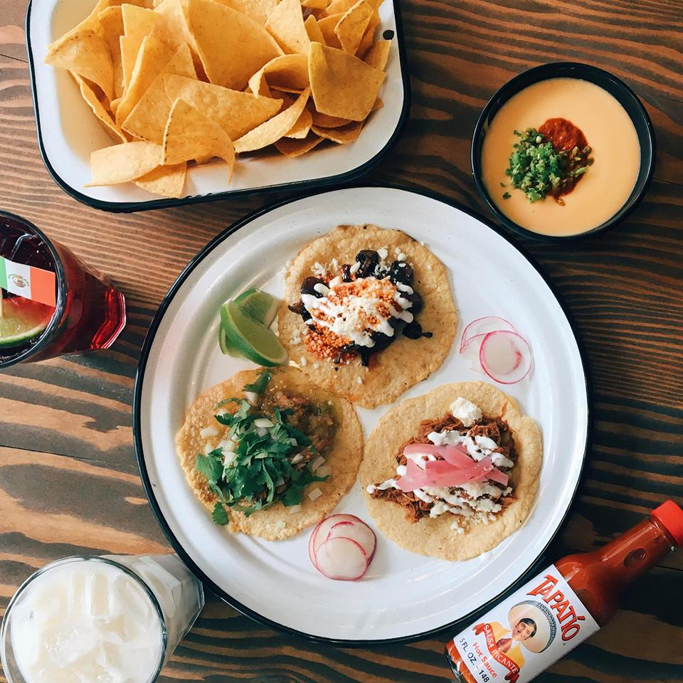 A top-down shot of several dishes at Little Neon Taco