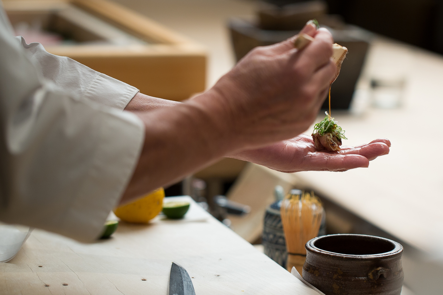 Chef Masa Takayama prepares sushi with his hands over a blond wood counter