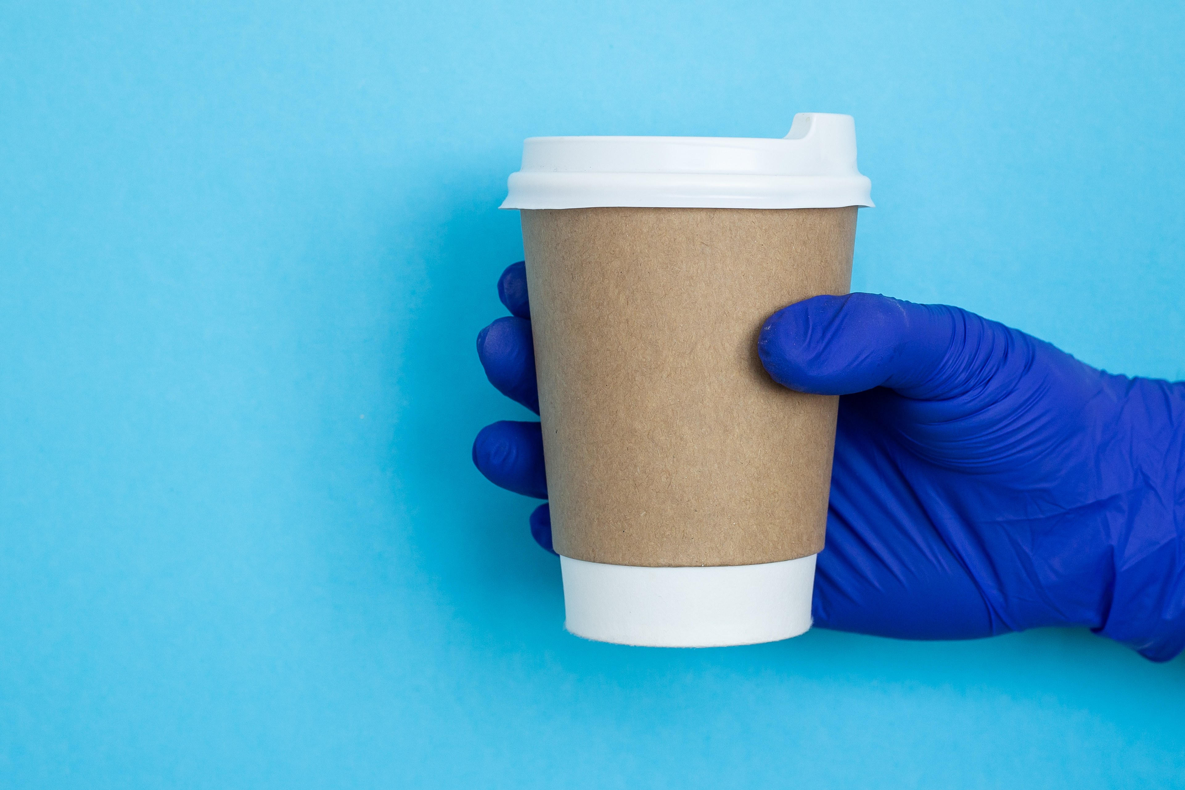 A gloved hand holding a paper cup of coffee