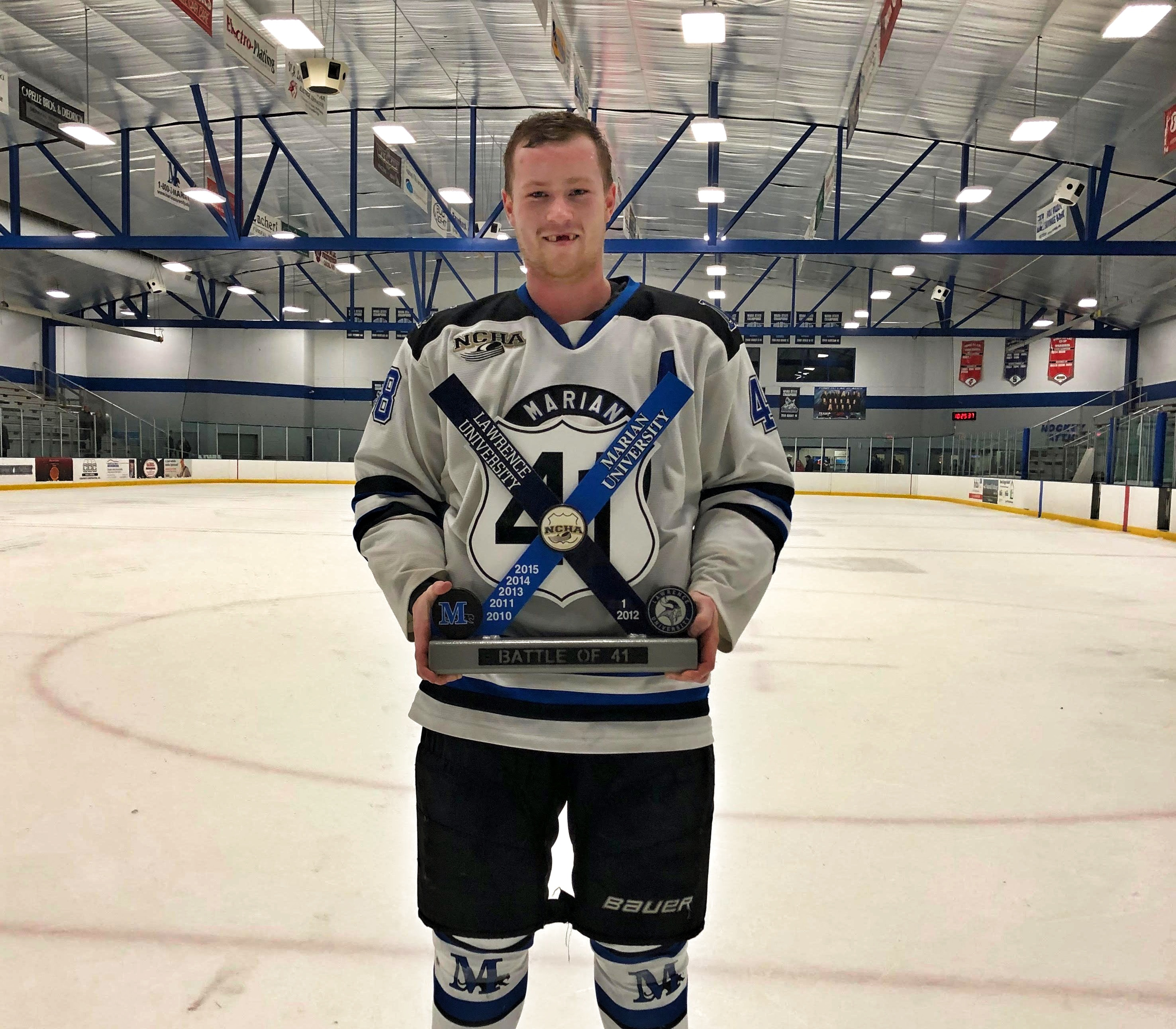 College hockey player Brock Weston holds a trophy.